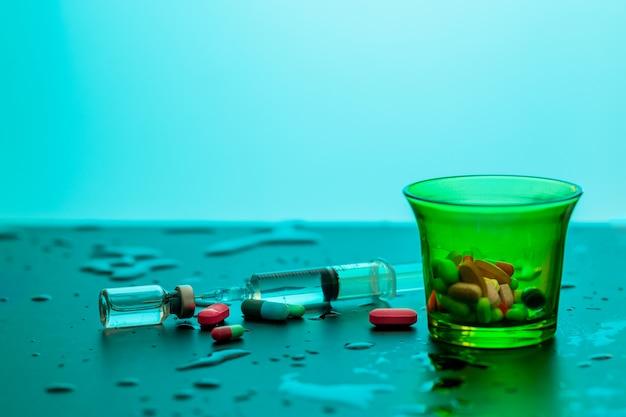 Copo de medição de cor verde com comprimidos dentro de uma seringa discada com um medicamento deitado entre gotas de água. conceito de saúde.