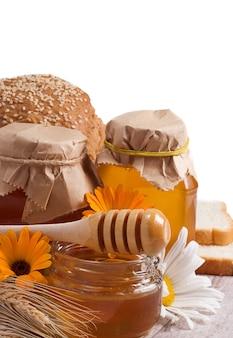 Copo de mel e pão isolado no branco