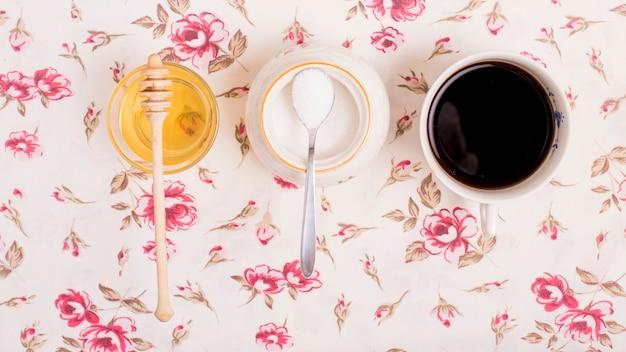 Copo de mel; leite em pó; e xícara de chá em pano de fundo floral