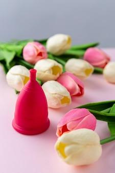 Copo de menstruação ao lado de tulipas