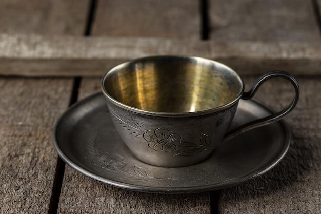 Copo de metal antigo para café em um pires
