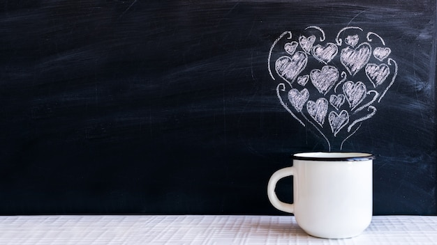 Copo de metal branco e pequenos corações desenhados a giz na forma de um coração