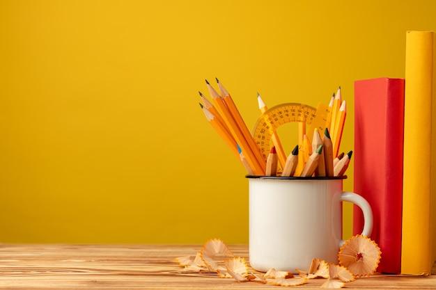 Copo de metal com lápis afiados e aparas de lápis na mesa de madeira contra amarelo