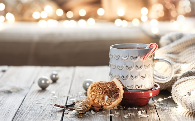 Copo de natal com bebida quente no fundo desfocado com bokeh.