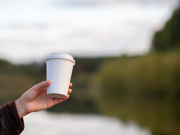 Copo de papel branco com café na mão da mulher. hora de tomar um café na cidade. café para viagem. aproveite o momento, faça uma pausa. close up do copo de papel descartável. deliciosa bebida quente. espaço em branco para texto, maquete
