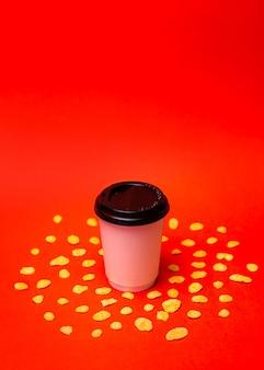 Copo de papel branco com flocos de milho em um fundo vermelho