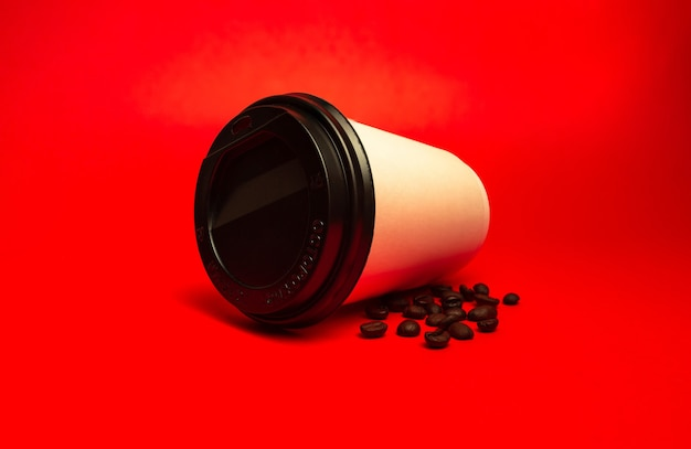 Copo de papel branco com grãos de café em um fundo vermelho