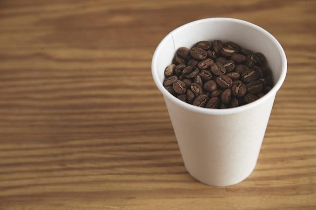 Copo de papel branco em branco com bons grãos de café torrados em uma mesa de madeira grossa em uma cafeteria