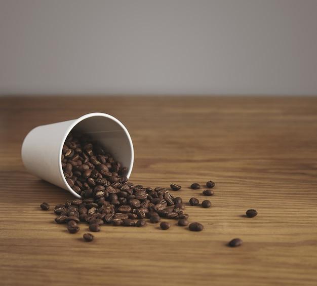 Copo de papel branco em branco com bons grãos de café torrados largado na mesa de madeira grossa em uma cafeteria
