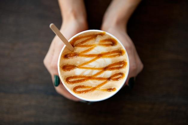Copo de papel caramelo grande café com leite na mão da mulher na mesa de madeira. bebida cappuccino ou latte, xícara de café na exibição plana de mesa. xícara de café com leite. pinturas de leite. café quente para menina