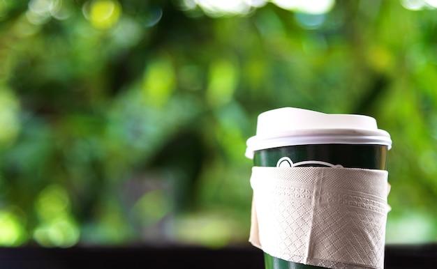 Copo de papel closeup de café quente na mesa de madeira com foco suave e mais luz no est