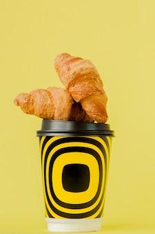 Copo de papel com café e croissants em um fundo amarelo, espaço de cópia