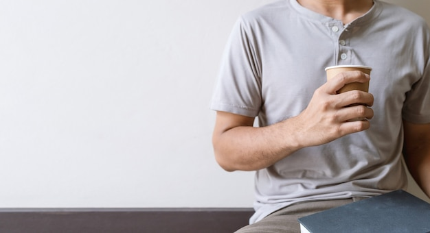 Copo de papel com café na mão para o homem na sala