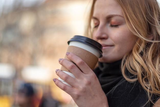 Copo de papel com café nas mãos da menina no fundo natural da manhã