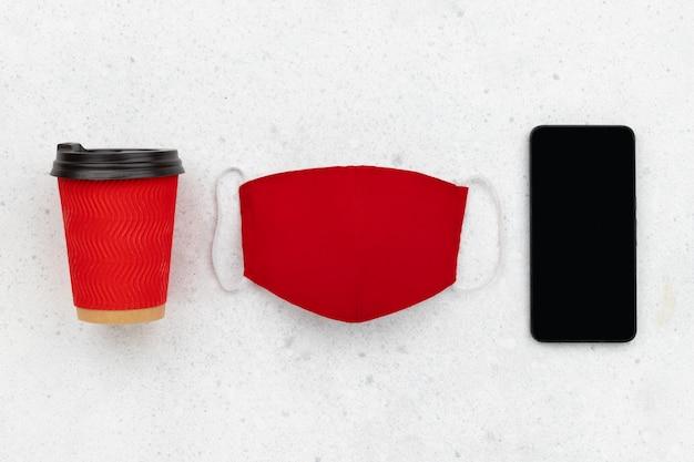Copo de papel com máscara facial e smartphone na mesa cinza. vista plana leiga nova composição normal de inverno outono.