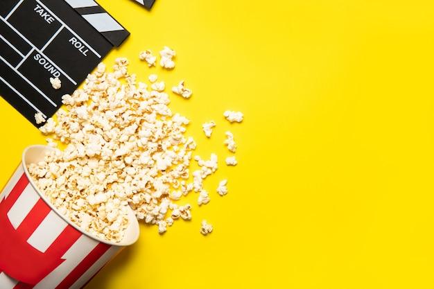 Copo de papel com pipoca e badalo de filme sobre um fundo amarelo, lugar para texto