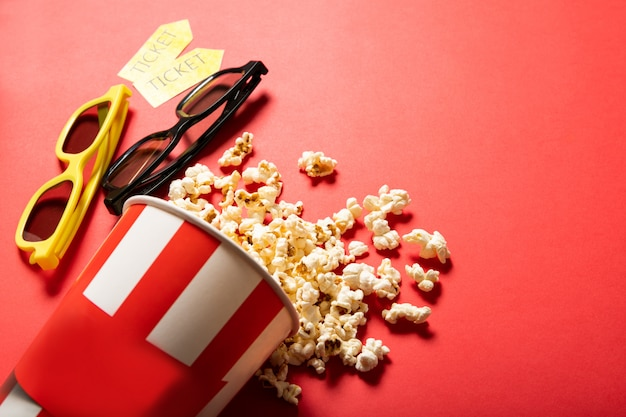 Copo de papel com pipoca em um fundo vermelho. pontos e ingressos de cinema