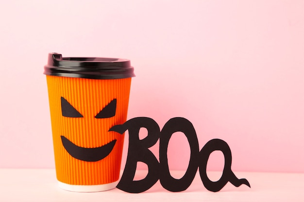 Copo de papel com rosto de halloween na superfície rosa com inscrição boo