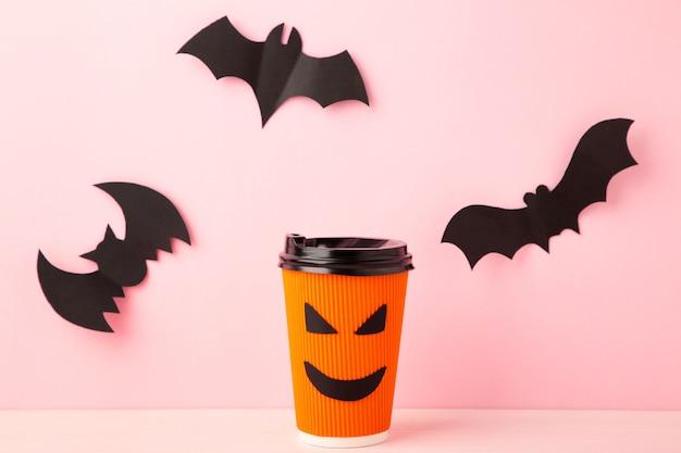Copo de papel com rosto de halloween na superfície rosa pastel com morcegos de halloween