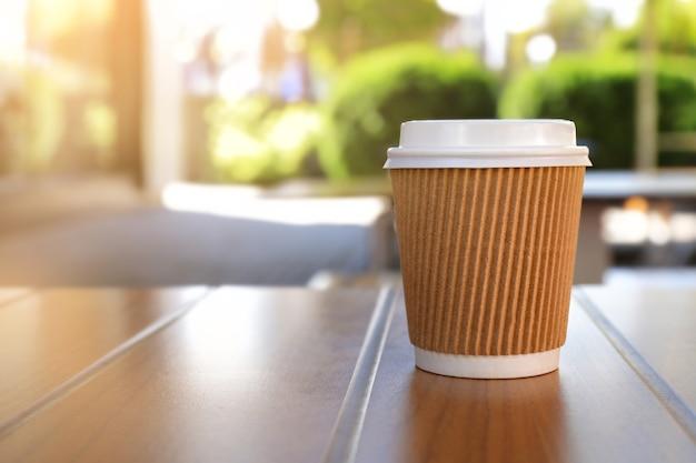 Copo de papel com saboroso café quente na mesa de madeira ao ar livre