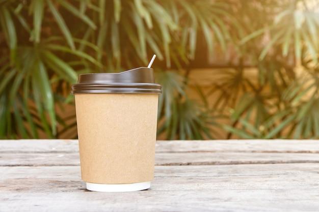 Copo de papel com tampa para café na mesa de madeira, café para viagem está na mesa fundo da natureza, há espaço para texto no fundo