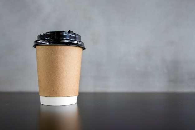 Copo de papel de café na mesa preta