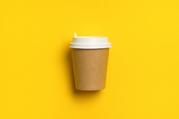 Copo de papel descartável com tampa para café e chá em um fundo amarelo pastel brilhante. pausa para café.