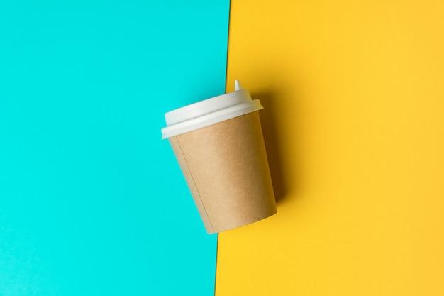 Copo de papel descartável com tampa para café e chá em um fundo azul e amarelo brilhante. pausa para café.