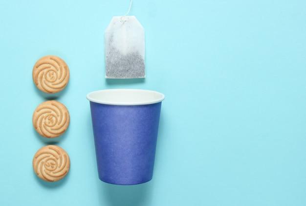 Copo de papel descartável vazio para chá, saquinho de chá, biscoitos na superfície azul pastel, vista superior, minimalismo