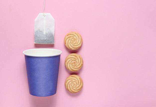Copo de papel descartável vazio para chá, saquinho de chá, biscoitos no fundo rosa pastel, vista superior, minimalismo