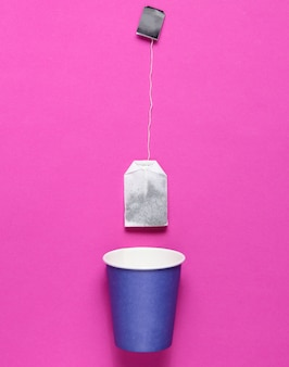 Copo de papel descartável vazio para chá, saquinho de chá em rosa, vista superior