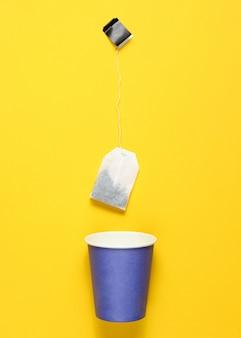 Copo de papel descartável vazio para chá, saquinho de chá na vista superior amarela