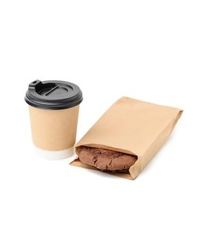 Copo de papel e biscoitos redondos com gotas de chocolate em uma sacola estreita de papel pardo, isolada no fundo branco, comida para viagem