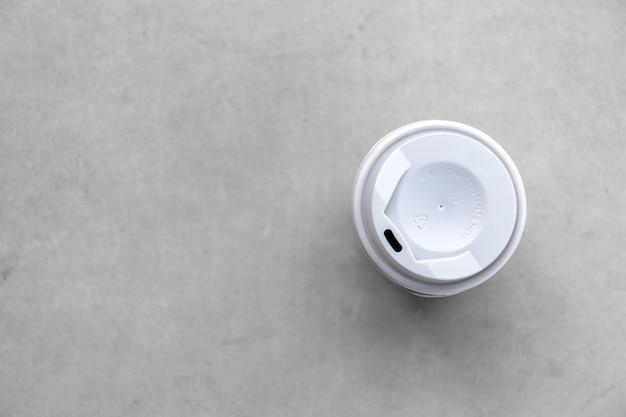 Copo de papel e café quente no fundo do chão de cimento. vista do topo