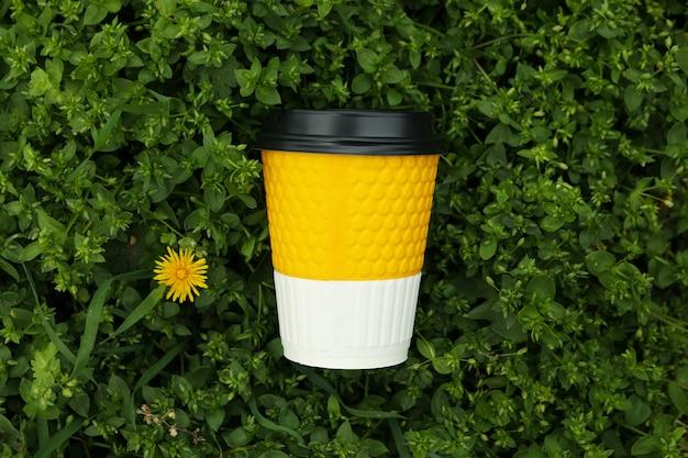 Copo de papel na grama verde fresca. taça para bebida