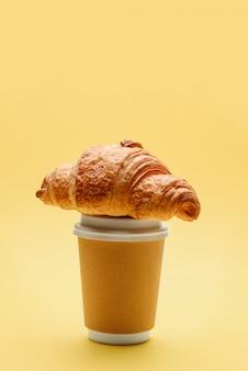 Copo de papel para café ou chá com um croissant na tampa