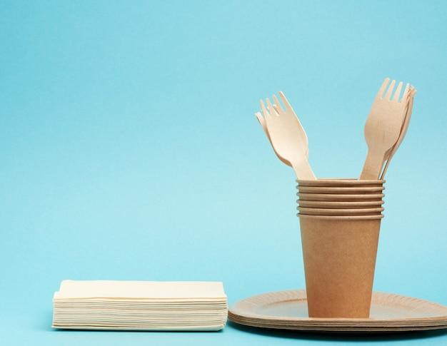 Copo de papel, pratos de papel artesanal marrom e garfos e facas de madeira sobre um fundo azul