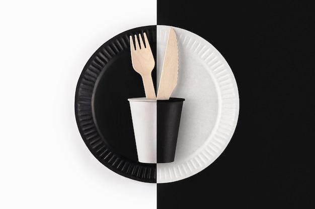 Copo de papel preto e branco com garfo de madeira e faca no prato de papel em fundo preto e branco, vista superior. talheres descartáveis ecológicos de material natural.