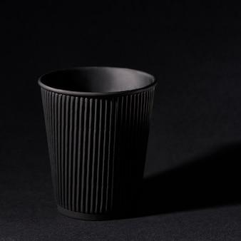 Copo de papel preto em pé no preto sólido