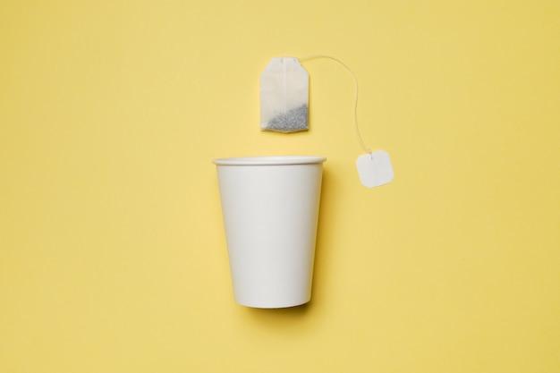 Copo de papelão branco com saquinho de chá em um fundo amarelo.