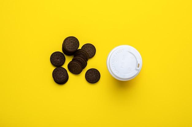 Copo de papelão com tampa e biscoitos de chocolate em um amarelo.