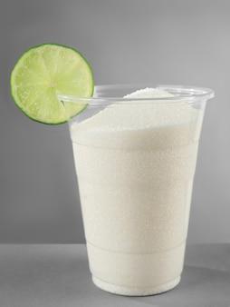 Copo de plástico cheio de açúcar com limão em fundo cinza