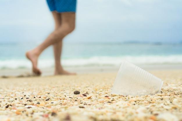 Copo de plástico na praia, andar de bicicleta