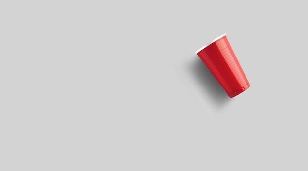 Copo de plástico vermelho isolado em cinza. conceito de jogo beer pong