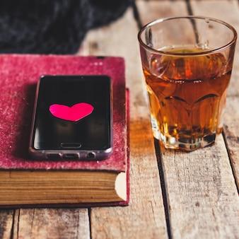 Copo de ponche de laranja, livro, smartphone e coração