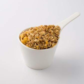 Copo de prato branco cheio de cereais amarelos.