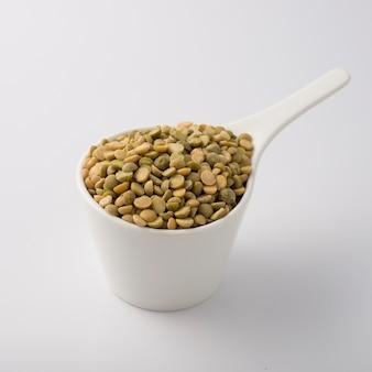 Copo de prato branco cheio de lentilha verde. isolado no branco. Foto Premium
