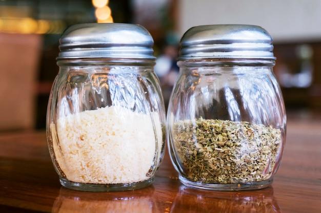 Copo de queijo sal e pimenta em mesa de madeira no restaurante