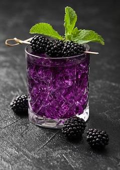 Copo de refrescante coquetel roxo de verão com amora, gelo e hortelã no fundo preto