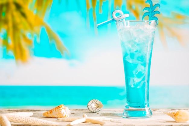 Copo de refrigerante bebida azul e estrelas do mar